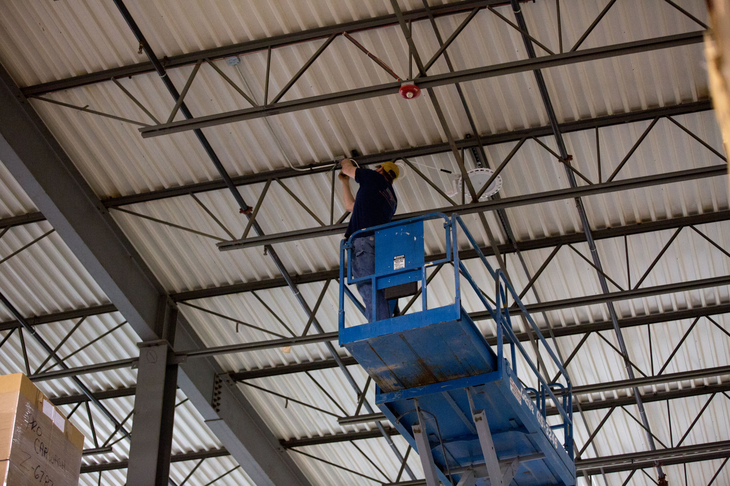 LED Emergency battery backup being installed in a warehouse by a man